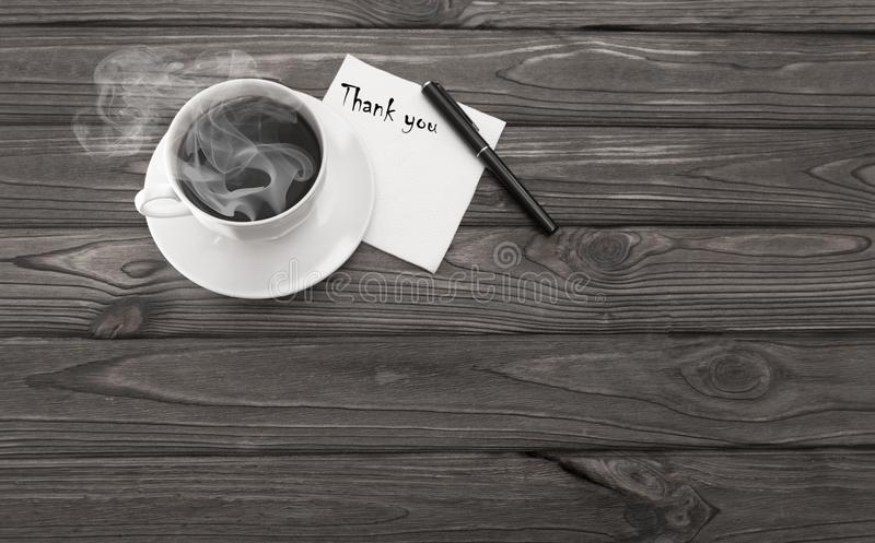 A cup of coffee, a napkin with an inscription thanks. On a wooden background stock photography