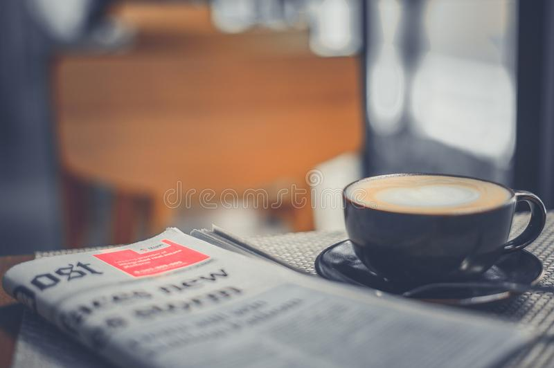 A cup of coffee and a newspaper of coffee on a wooden table stock images