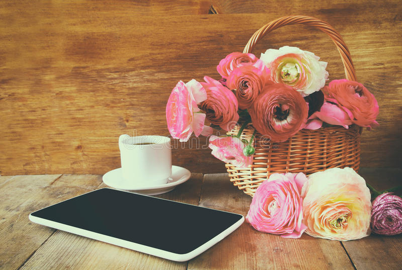 Cup of coffee next to tablet and flowers on wooden table stock photos
