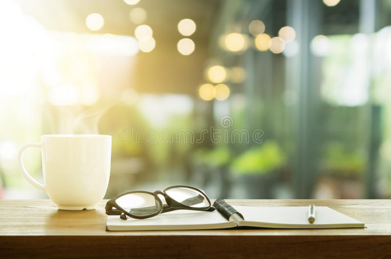 Cup of coffee and note book on wooden table. Coffee break in morning. stock photos
