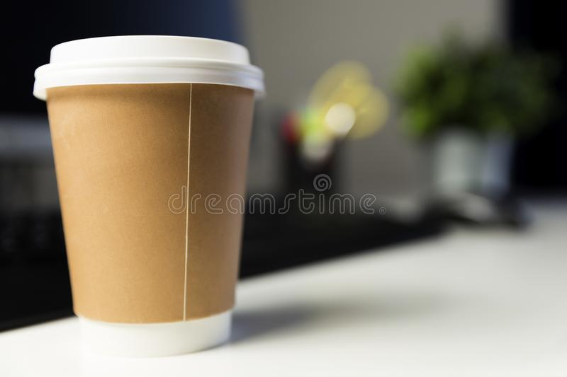 Cup of coffee in office next to computer. Working late concept stock photos
