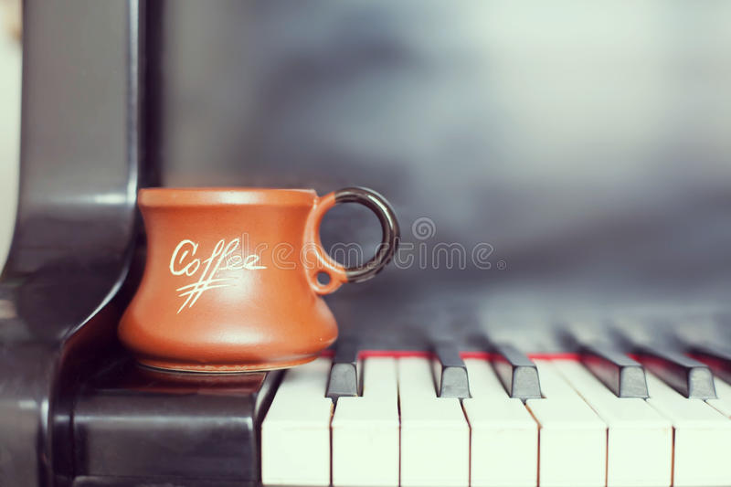 Cup of coffee on an old piano keyboard while composing. Evening time and some sun rays. Coffee mug on the piano keyboard stock photo