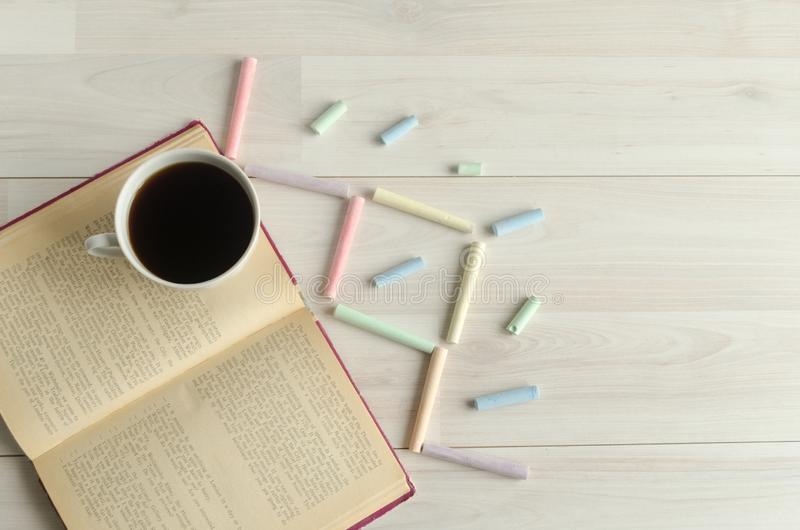 A cup of coffee, an open book and multicolored chalks on a white wooden background.World book day,copyspace. stock image