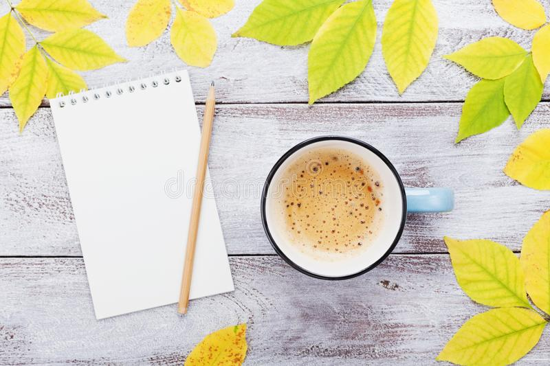 Cup of coffee, open empty notebook and autumn leaves on vintage wooden table top view. Cozy breakfast. Fall bucket list. Flat lay. Style stock photos