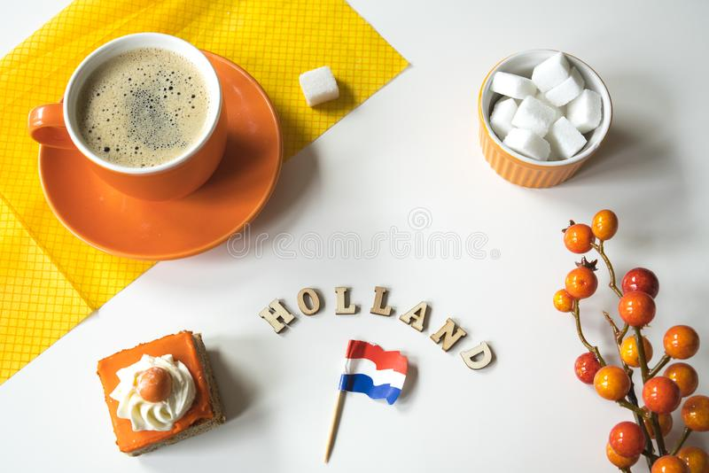 Cup of coffee, orange cake and eclair. Traditional treat for Dutch event Kings Day, Koningsdag. Cup of coffee and cake with orange frosting, eclaire.  wooden royalty free stock photos