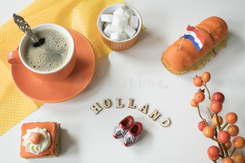 Cup of coffee, orange cake and eclair. Traditional treat for Dutch event Kings Day, Koningsdag stock photos