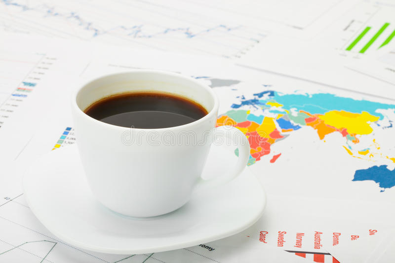 Cup of coffee over world map and financial documents. Studio shot royalty free stock photo