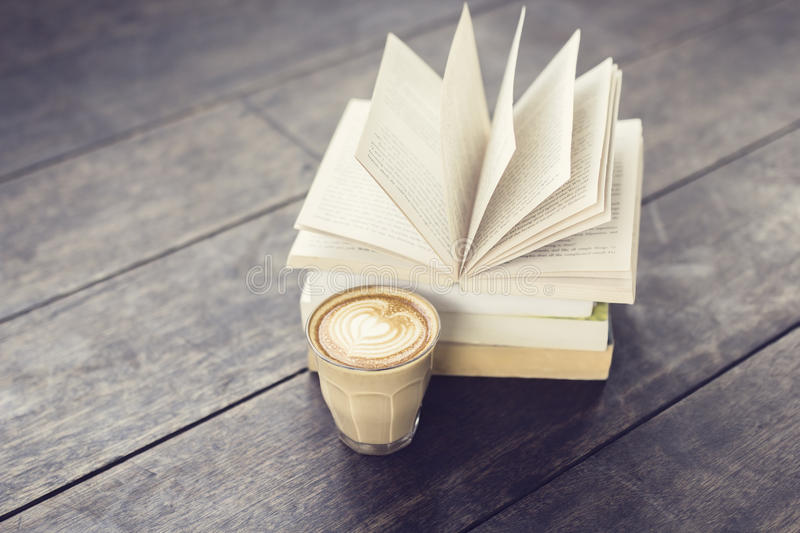 Cup of coffee and pack of books on vintage style floor royalty free stock photos
