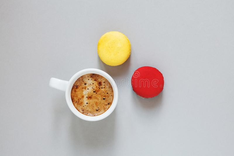 Cup of coffee and pair of colorful macarons or macaroons on gray background, top view stock photo