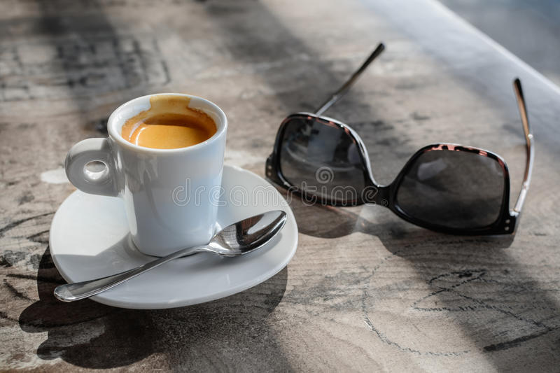 Cup of coffee and pair of glasses on vintage table. Soft focus w royalty free stock photos