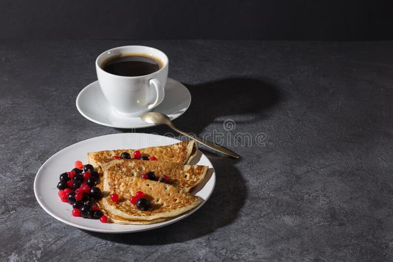 A cup of coffee and pancakes with berries on a teel. Delicious breakfast stock images