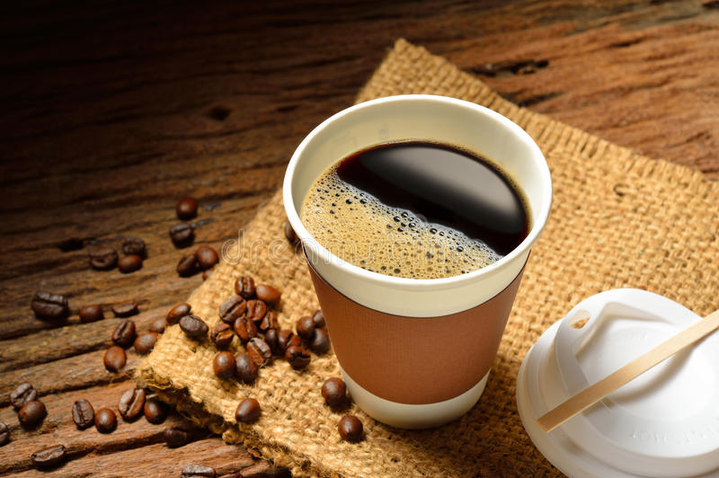 Cup of coffee. Paper cup of coffee and cake on wooden background stock images