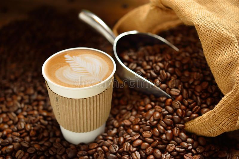 Cup of coffee. Paper cup of coffee latte and coffee beans on wooden table stock image