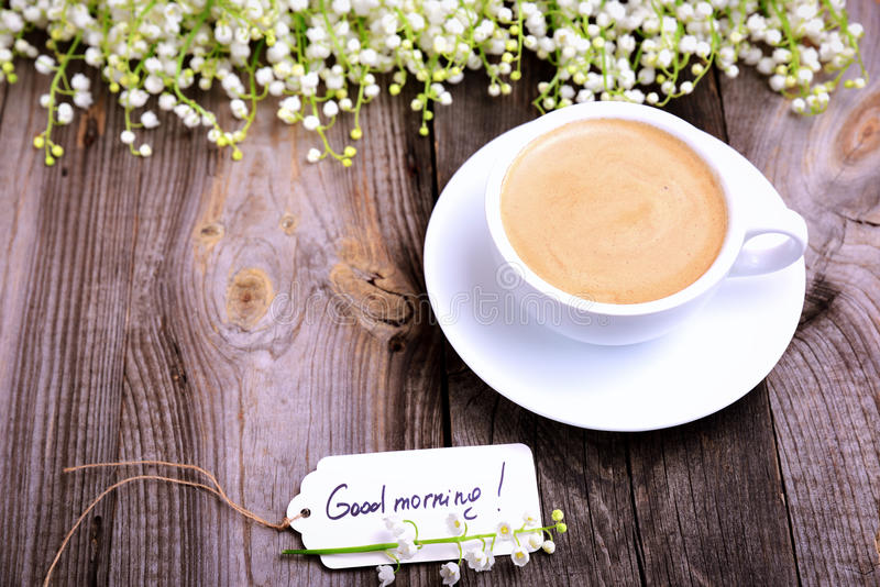 Cup of coffee and a paper tag with the inscription good morning. Gray wood background royalty free stock images