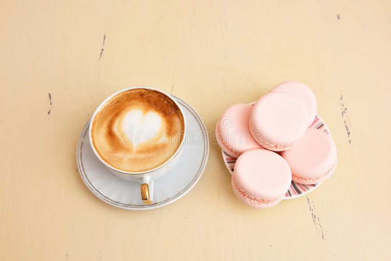 Cup of coffee with a pattern of hearts and macaroons on a vintage table stock images