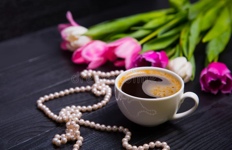 Cup of coffee, pearl necklace and bouquet of tulips on black woo stock photography
