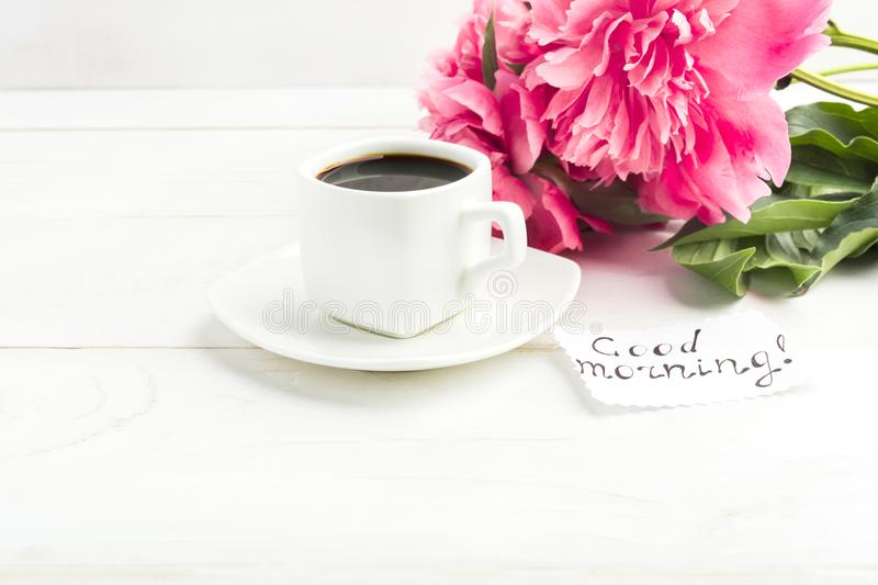 A cup of coffee with peony flowers and note `Good morning` on wh. Ite wooden table wtih copy space royalty free stock image