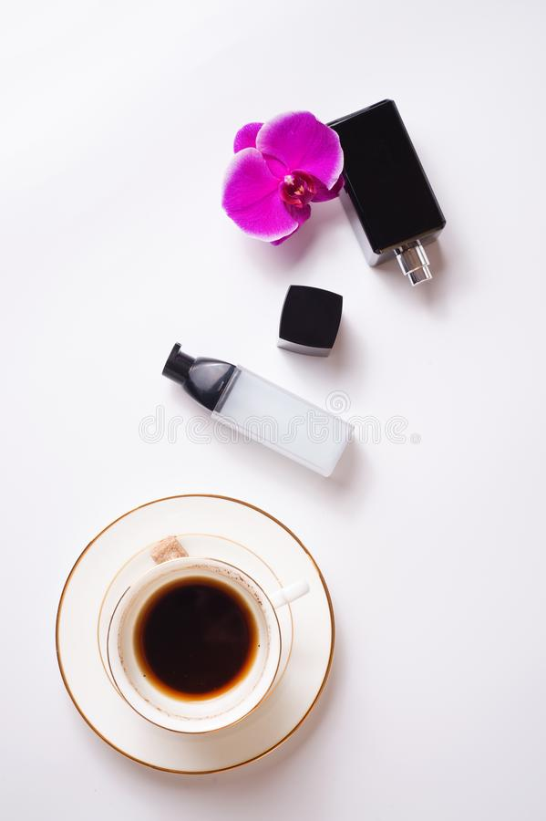 Cup of coffee with perfume and care essence around white background. life style flat lay stock photography