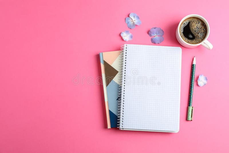 Cup of coffee with petals of flower, copybooks and pen on color background stock image