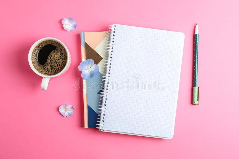 Cup of coffee with petals of flower, copybooks and pen on color background royalty free stock images