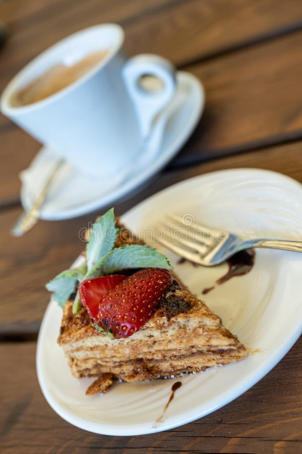 A cup of coffee and a piece of honey sponge cake decorated with strawberries and mint on a wooden table. A cup of black coffee and a piece of honey sponge cake stock photos