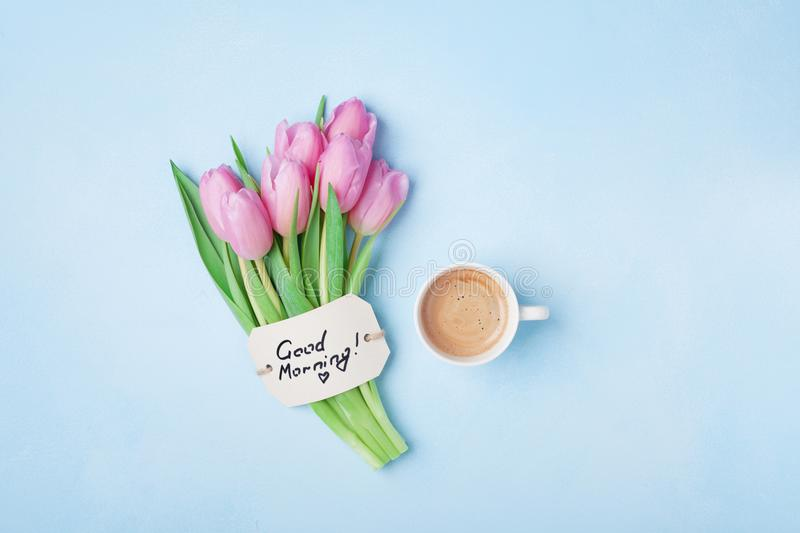 Cup of coffee, pink tulip flowers and note good morning on blue table top view. Beautiful breakfast on Mothers or Womans day. Cup of coffee, pink tulip flowers stock photography