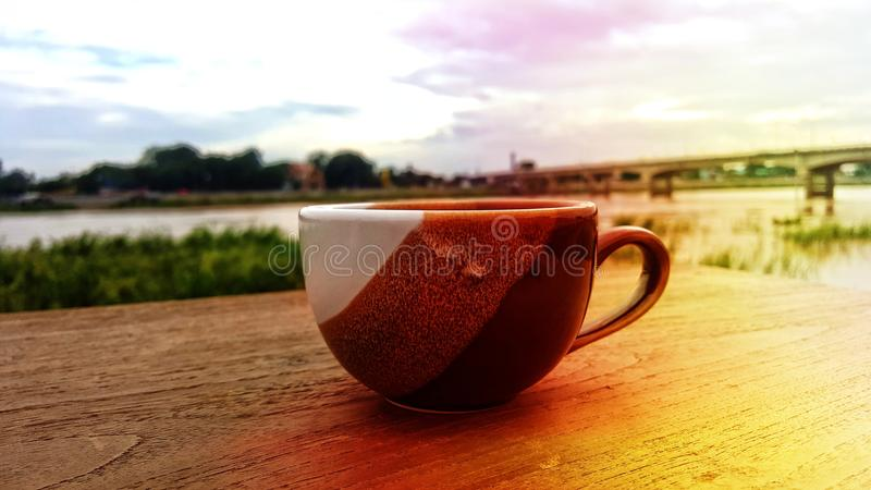 A cup of coffee is placed on a wooden floor. The background overlooks the bridge and the river. The orange sun shines down royalty free stock images