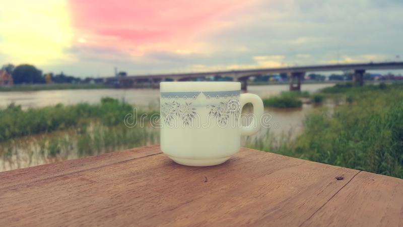 A cup of coffee is placed on a wooden floor in the morning. A cup of coffee is placed on a wooden floor. The background overlooks the bridge and the river. The royalty free stock image