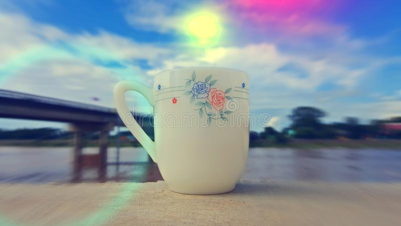 A cup of coffee is placed on a wooden floor in the morning. A cup of coffee is placed on a wooden floor. The background overlooks the bridge and the river. The stock images