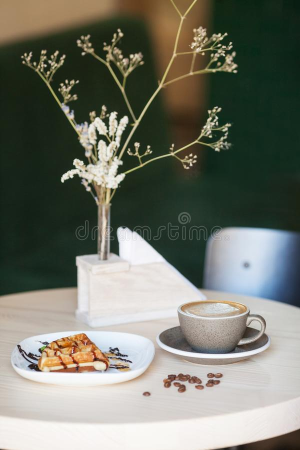 Cup of coffee and plate of belgian waffles on light wooden table stock photo