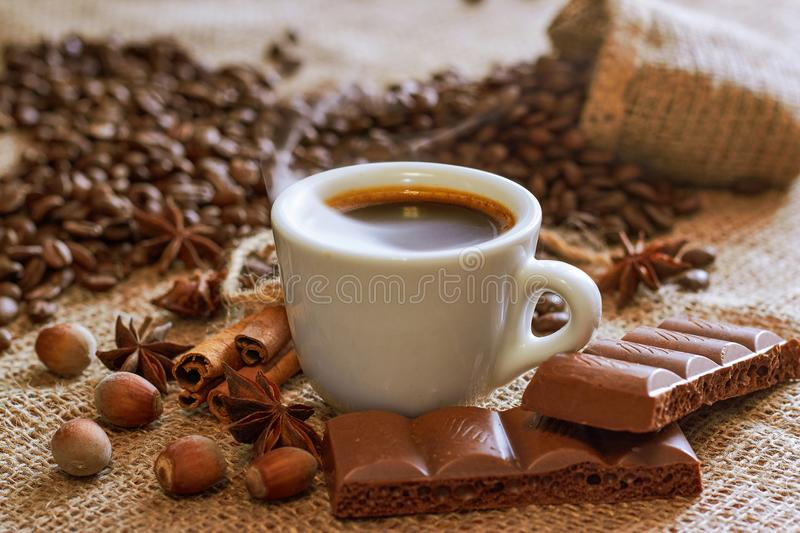 A cup of coffee on a plate with cinnamon and anise and chocolate, grains of coffee on sackcloth stock photo