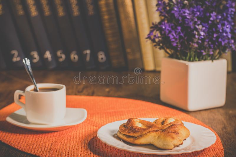 A cup of coffee and a plate with pastries royalty free stock image
