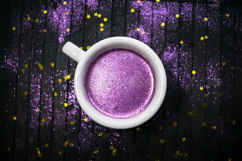Cup of coffee with purple glitter on dark background with golden royalty free stock photos