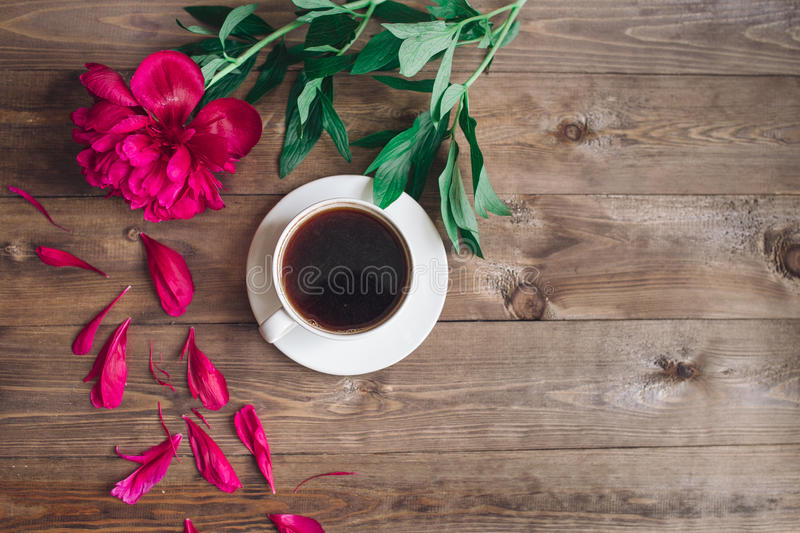 A cup of coffee , red peonies pattern on wooden background . Good morning .Women`s or Mother`s Day background. Top view. A cup of coffee , red peonies pattern royalty free stock photos