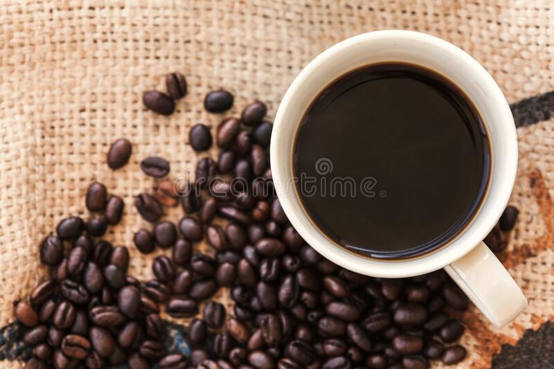 Cup of coffee and roasted coffee beans are on jute bag royalty free stock photography