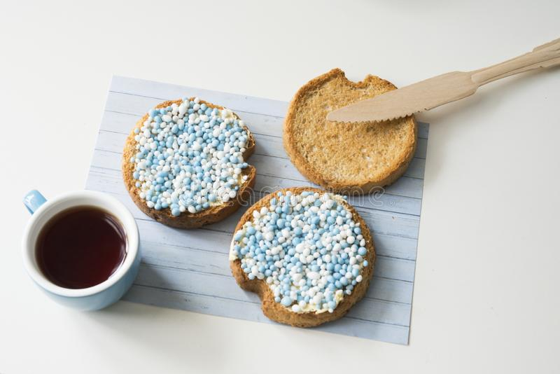 Rusk with blue aniseed balls, muisjes, Dutch treat for when a baby boy is born in The Netherlands. Cup of coffee, rusk  with blue and white aniseed sprinkles royalty free stock images