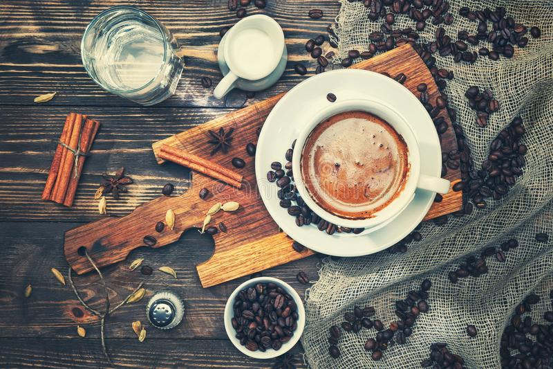 A cup of coffee on a rustic wooden table with spices, cinnamon, milk, water, salt, coffee beans. Toned royalty free stock photos