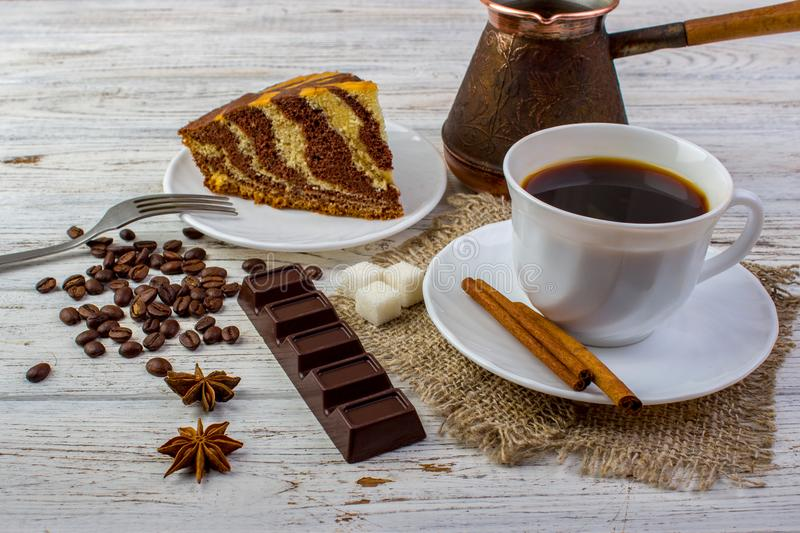 A cup of coffee on sacking with tasty chocolate cake on a plate. Cinnamon sticks, sugar, coffee beans, a chocolate bar, anice on b royalty free stock images
