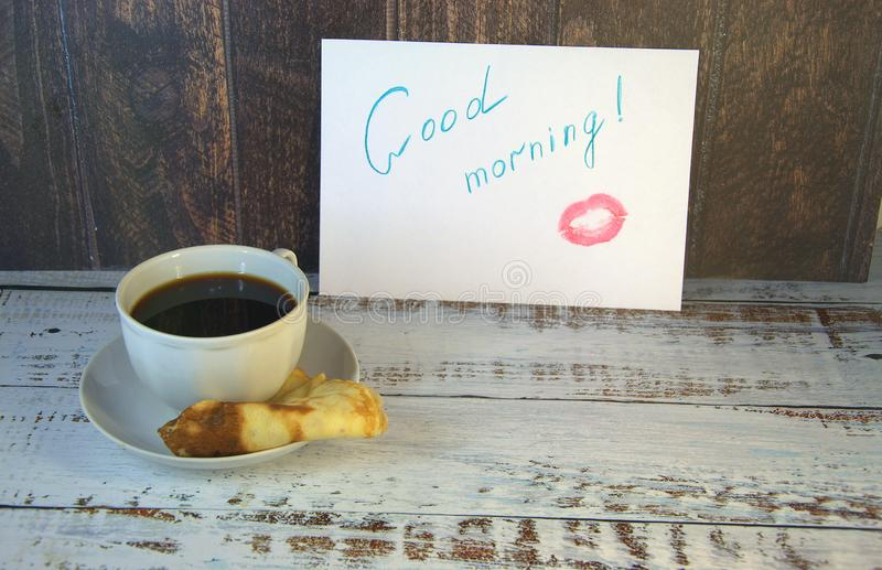 A cup of coffee on a saucer, a freshly baked pancake and a piece of paper with a wish of good morning and a trace of lipstick. Close-up stock images