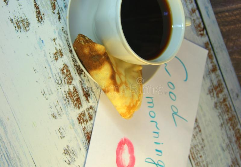 A cup of coffee on a saucer, a freshly baked pancake and a piece of paper with a wish of good morning and a trace of lipstick. Close-up royalty free stock photos