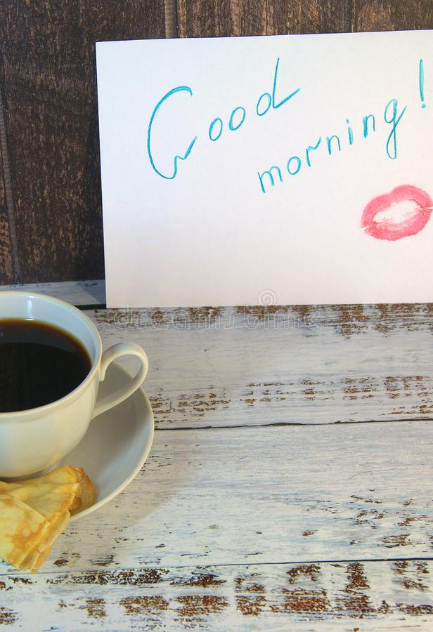 A cup of coffee on a saucer, a freshly baked pancake and a piece of paper with a wish of good morning and a trace of lipstick. Close-up royalty free stock photo