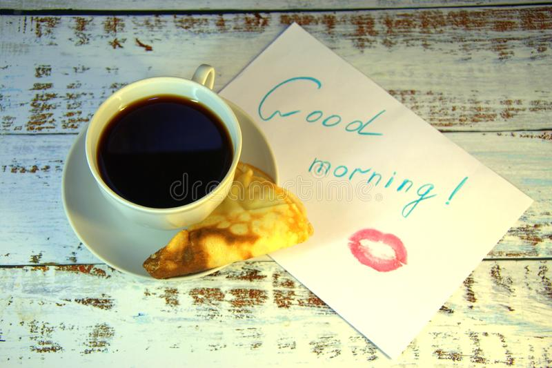 A cup of coffee on a saucer, a freshly baked pancake and a piece of paper with a wish of good morning and a trace of lipstick. Close-up royalty free stock photography