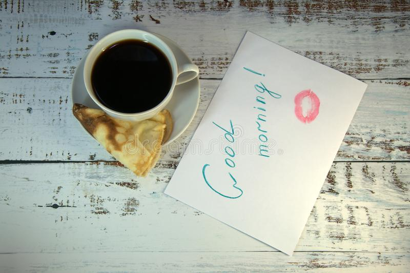 A cup of coffee on a saucer, a freshly baked pancake and a piece of paper with a wish of good morning and a trace of lipstick. Close-up stock image