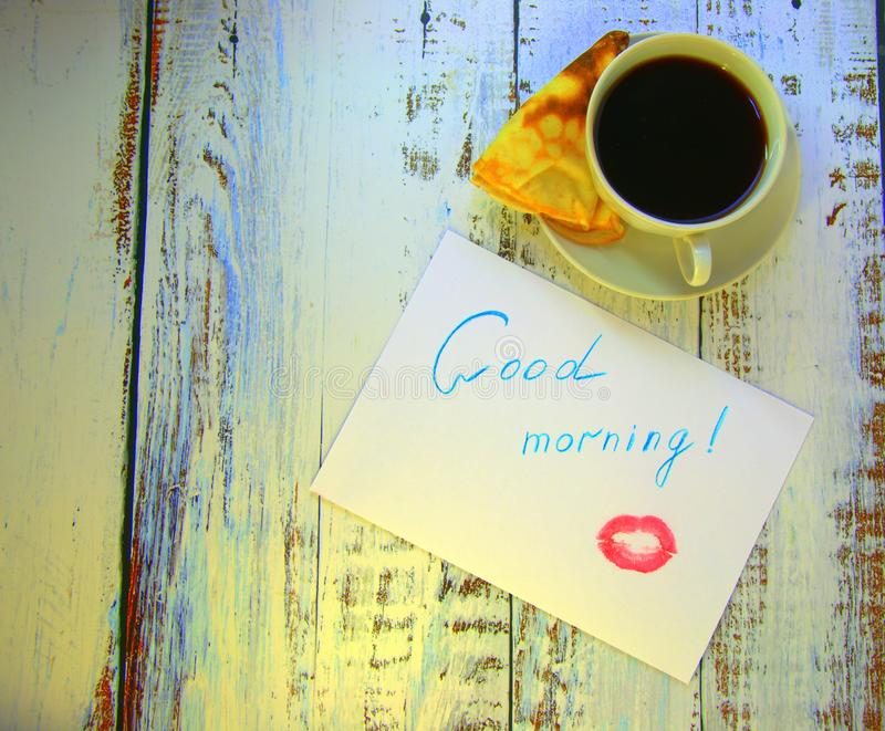 A cup of coffee on a saucer, a freshly baked pancake and a piece of paper with a wish of good morning and a trace of lipstick. Close-up stock photography