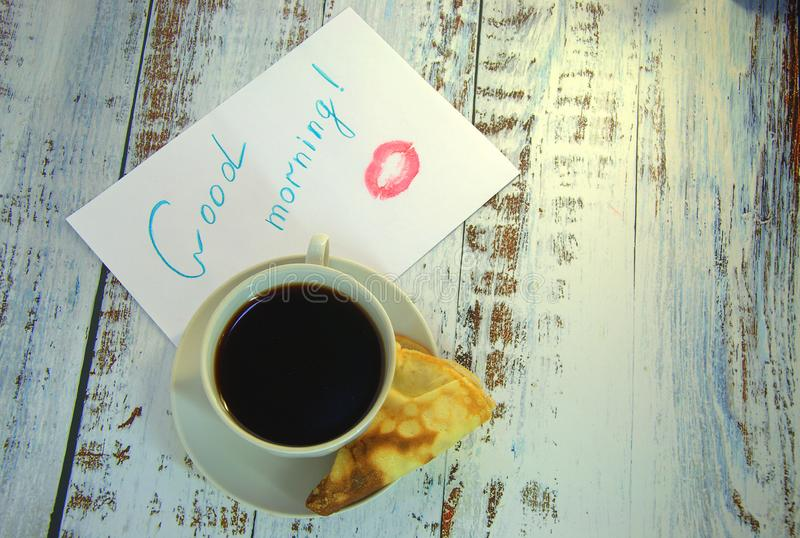 A cup of coffee on a saucer, a freshly baked pancake and a piece of paper with a wish of good morning and a trace of lipstick. Close-up royalty free stock images