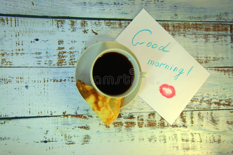 A cup of coffee on a saucer, a freshly baked pancake and a piece of paper with a wish of good morning and a trace of lipstick. Close-up stock photo