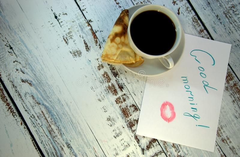 A cup of coffee on a saucer, a freshly baked pancake and a piece of paper with a wish of good morning and a trace of lipstick. Close-up stock photos