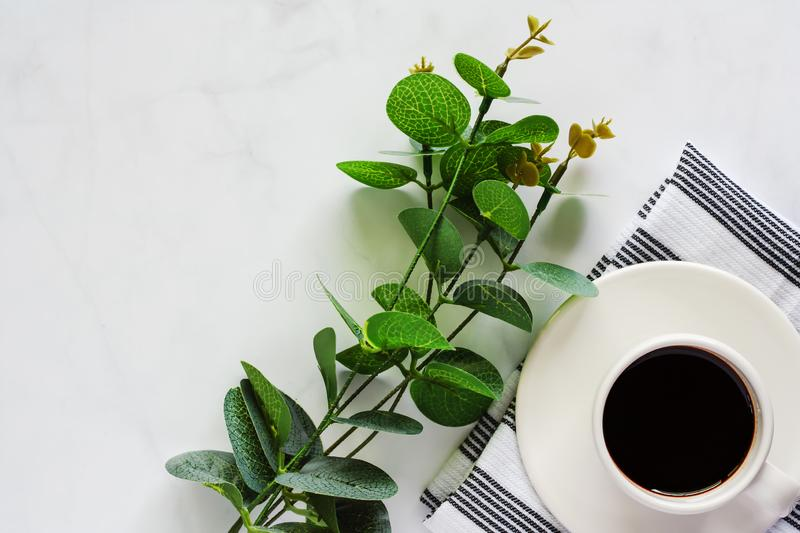 Cup of coffee with saucer, napery, leaf bouquet on white marble. Background for drinks and beverage concept stock photo