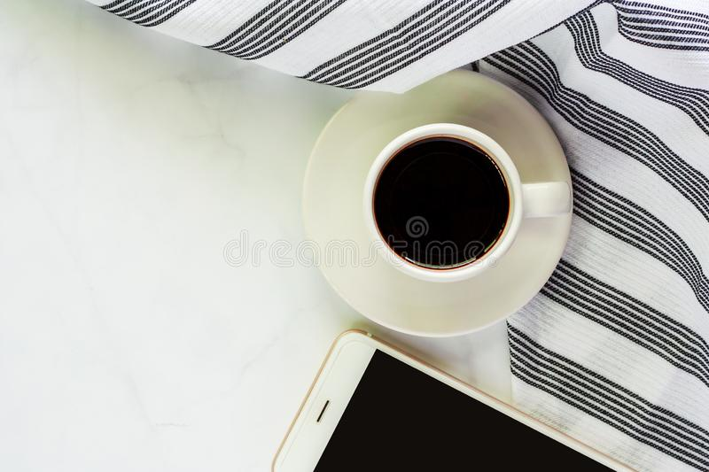 Cup of coffee with saucer, napery and smartphone on white marble royalty free stock image