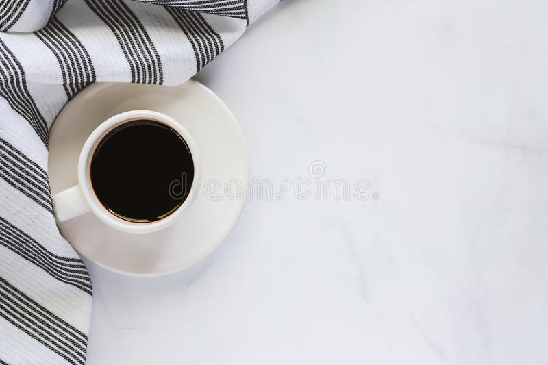 Cup of coffee with saucer and napery on white marble background. For drinks and beverage concept stock photo